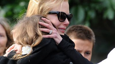 The 'Moulin Rouge' star clutches onto one of her sister's children as she farewells her father.