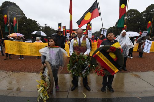 Members of the Frontier war contingent prepare to lay a wreath at the stone of remembrance at the end of the ANZAC Day march at the Australian War Memorial in Canberra.