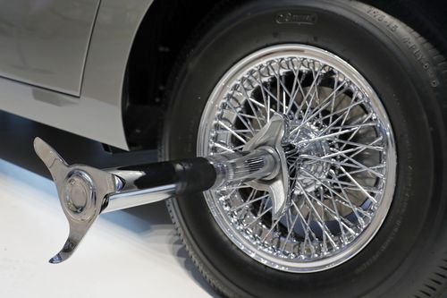 A tire slasher inspired by the chariots from Ben Hur extends from a rear wheel of the Aston Martin.
