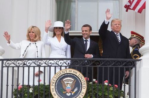 First ladies Brigette Macron and Melania Trump join their husbands as they wave to the crowd. (AAP)