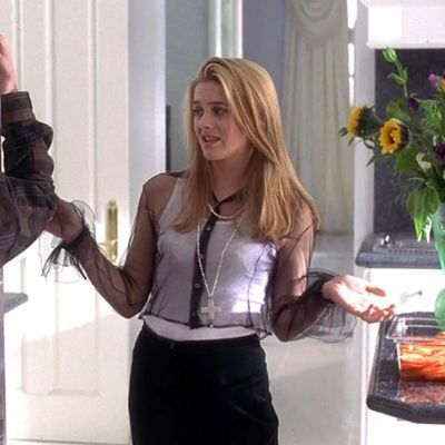 Cher Horowitz in a black sheer blouse, white crop top and over-sized cross necklace. <em>Clueless</em> 1995