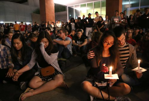 Student mourners console each other during a candlelight vigil at the University of Nevada Las Vegas. (AAP)