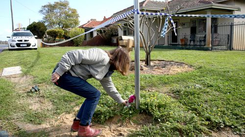 A woman lays flowers at the Perth home where the family was found dead.