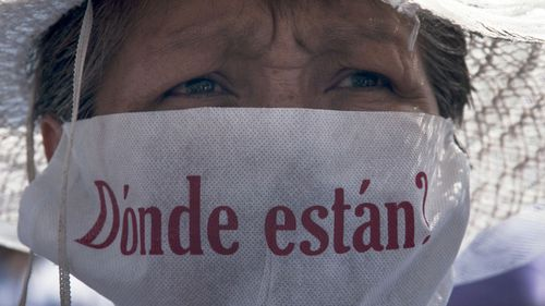 "A mother with a face mask that reads in Spanish ""Where are they?"" marches along with hundreds of other mothers holding images of their missing relatives during Mother's Day, in Mexico City, Sunday, May 10, 2015. Mothers and other relatives of persons gone missing in the fight against drug cartels and organized crime are demanding that authorities locate their loved ones."