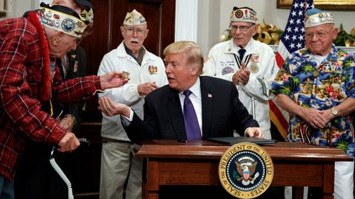 Lawrence Parry, left, shows a challenge coin to President Donald Trump. (AAP)