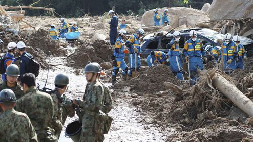 Self-Defense Force officials and policemen conduct a search operation for missing people in Kumano Town. (AAP)