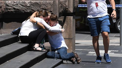 People are seen hugging on the corner of Bourke and Elizabeth street after a rogue car ploughed through pedestrians at Bourke Street Mall in Melbourne on January 20, 2017. (AAP)