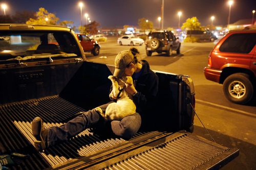 Paradise teacher Sarah Gronseth kisses her dog Branch while resting in the bed of a truck.