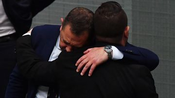 MPs Gavin Pearce (left) and  Phillip Thompson embrace in the House of Representatives.