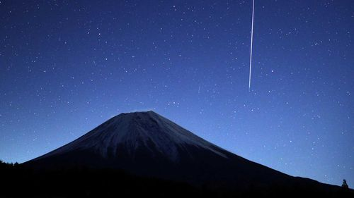 A meteor enters the Earth's atmosphere near Mount Fuji, Japan.
