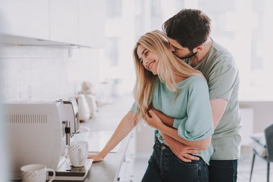 Bearded guy standing behind blonde girl and kissing her. They are waiting for hot drink