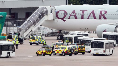 Police and emergency services surround the Qatar Airways plane that was subject to a bomb threat. (AAP)