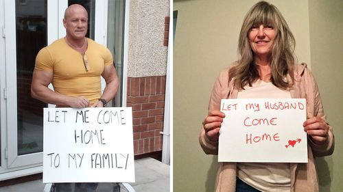 Mr and Mrs Tomlinson carrying signs as part of the #letthemcomehome campaign taken up by the thousands of temporary residents trying to get back to Australia.