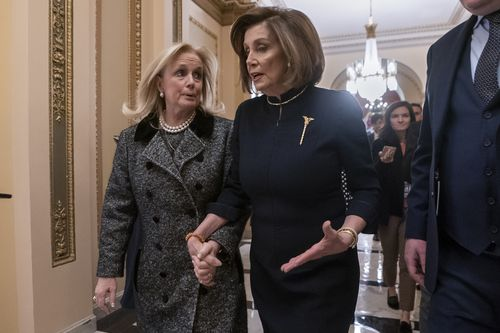 Speaker of the House Nancy Pelosi holds hands with Debbie Dingell, left, as they walk to the chamber ahead of the debate.