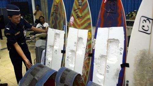A customs officer inspects surfing boards used by Brazil's citizen Rodrigo Gularte to smuggle six kilograms of cocaine. (AAP)
