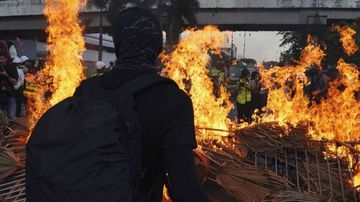 Protestors trample Chinese flag, set a street on fire