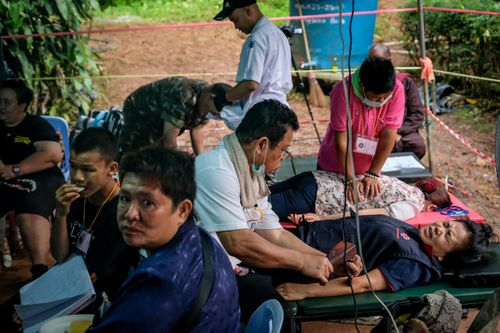 Traditional massage therapy is given to family and rescue crews at the makeshift camp. (Getty)
