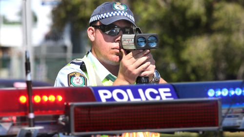 A NSW police officer zeroes his speed camera on cars. The NSW government is considering ditching speed camera warning signs in a move that it claims could save lives.
