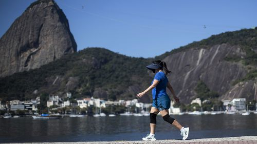 A woman walks past Sugarloaf Mountain in Rio de Janeiro, Brazil.