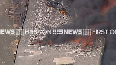 The fire quickly spread to the factory roof, with flames and heat forcing the roof to implode. (9NEWS)