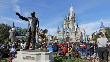 FILE - In this Jan. 9, 2019 photo, guests watch a show near a statue of Walt Disney and Micky Mouse in front of the Cinderella Castle at the Magic Kingdom at Walt Disney World in Lake Buena Vista, part of the Orlando area in Fla.  (AP Photo/John Raoux, File)