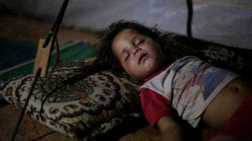 In this 2017 file photo, Saja Salih, 3, sleeps in her tent in the Hassan Sham camp for displaced people in Northern Iraq. Earlier that year, her family home in Mosul was destroyed by an air strike.