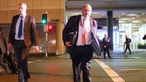 John Lyons (second right), Executive Editor of ABC News, watches as two Australian Federal Police officers cross the road outside the ABC building.