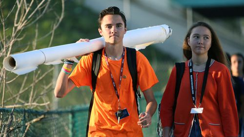 Marjory Stoneman Douglas student David Hogg walks to school with a large rolled banner over his shoulder on April 20, 2018 in Parkland, Florida. (AP)