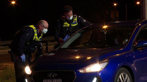 Polisi memeriksa mobil yang mencoba melintasi perbatasan Victoria di Albury sebelum penutupan tengah malam.