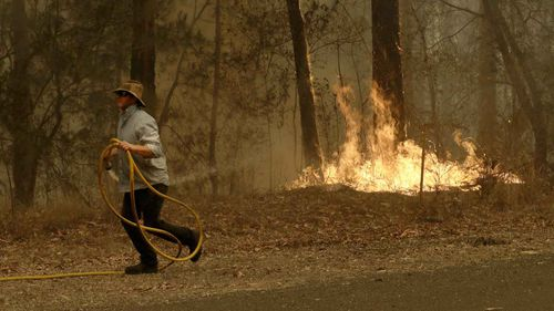 A man runs back to his truck after trying to quench a fire near Moruya, Australia.