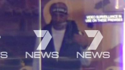 The first image of the alleged gunman who has taken hostages inside a Sydney cafe.