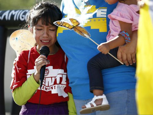 Akemi Vargas, 8, cries as she talks about being separated from her father during an immigration family separation protest in front of the Sandra Day O'Connor U.S. District Court building. (AAP)