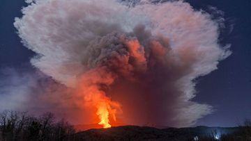 A fiery river of glowing lava flows on the north-east side of the Mt Etna volcano engulfed with ashes and smoke near Milo, Sicily, Wednesday night, Feb. 24, 2021. Europe's most active volcano has been steadily erupting since last week, belching smoke, ash, and fountains of red-hot lava.