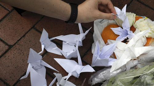A mourner places paper birds near the flowers on the site where a man fell to his death a day earlier after hanging a protest banner on the scaffolding of a shopping mall in Hong Kong.