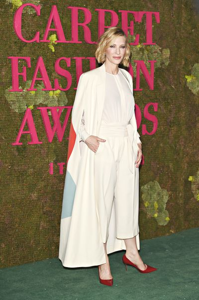 Cate Blanchett wears a white shirt, high-waist pants and cape by Stella McCartney. The look has been taken from the Green Carpet Collection from 2014. The look has been hand printed with certified water-based inks, RWS certified sustainable wool and GOTS certified organic silk fabric
