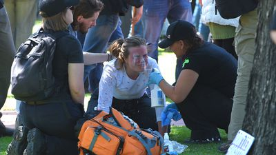 Anti-racism protesters from the Campaign Against Racism and Fascism group are treated with milk after being capsicum-sprayed. (AAP)
