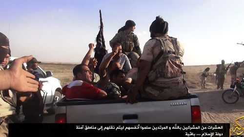 A photograph made available by the jihadist affiliated group Albaraka News allegedly shows ISIL fighters taking away Iraqi soldiers near the border between Syria and Iraq in 2014.