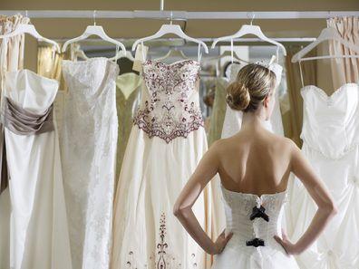 Bride standing in front of wedding dresses