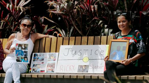 Beryl Dixon and Tiara Kelly, mother and sister of victim Ricky Slater, pose with a tribute to Ricky, outside Newcastle Court.