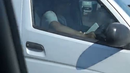 The driver was recorded with a book in one hand, and the steering wheel of the other van in the other.