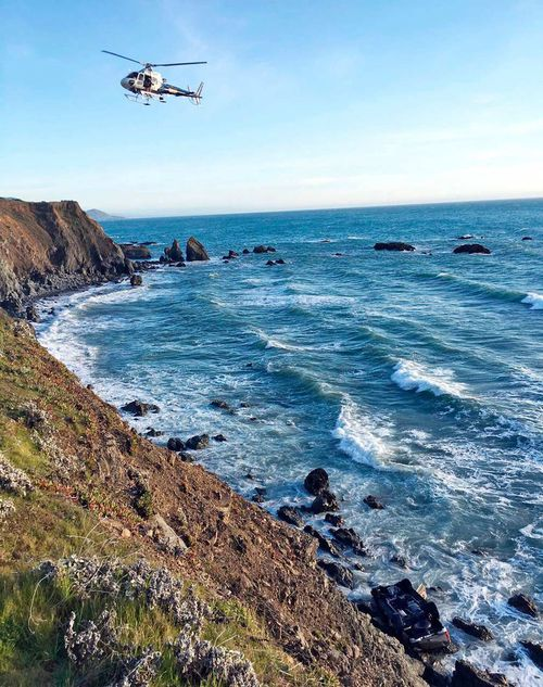 A helicopter hovering over steep coastal cliffs near Mendocino, California where the SUV went off the road
