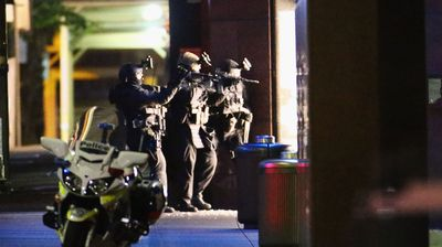 Armed police begin to move in shooting down the door to the Lindt Cafe. (Getty)