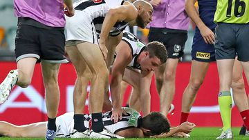 Brody Mihocek of the Magpies lies still on the ground after a collision