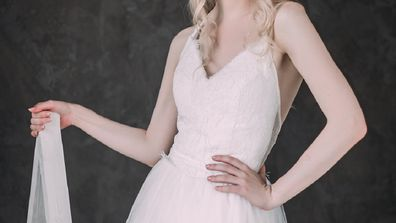 Portrait of a beautiful blond girl in image of the bride . Beauty face. Photo shot in the Studio on a grey background