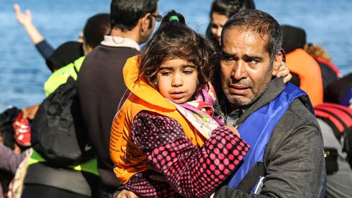 A man holds a girl after their arrival on a dinghy from the Turkish coast to the Greek island of Lesbos. (AAP)