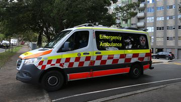 An ambulance is seen departing a housing tower on Morehead Street in Redfern. Health authorities are working to contain an emerging COVID-19 cluster across three social housing towers in the inner-city suburb.