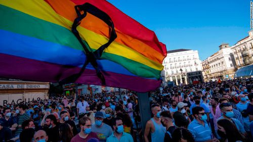 The rainbow flag with a black ribbon flutters during a protest against the killing of Samuel Luiz in the Puerta del Sol in central Madrid, Spain.