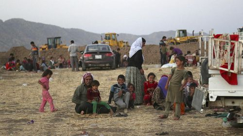 Displaced Iraqis from the Yazidi community settle outside the camp of Bajid Kandala at Feeshkhabour town near the Syria-Iraq border. (AP Photo/ Khalid Mohammed)