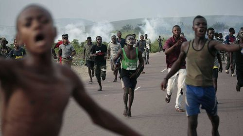 Supporters of opposition candidate Martin Fayulu run from tear gas fired by police in Nsele, 50kms east of Kinshasa, Democratic Republic of the Congo yesterday.