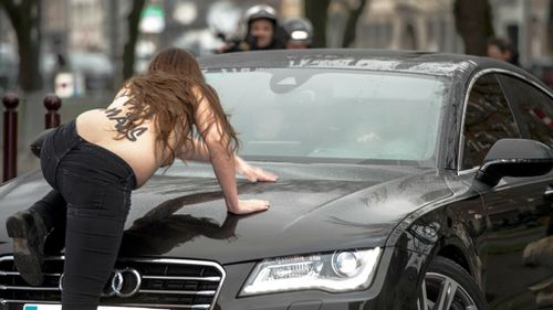 A topless Femen activist climbs on top of a car carrying former IMF boss Dominique Strauss-Kahn to court. (Getty)